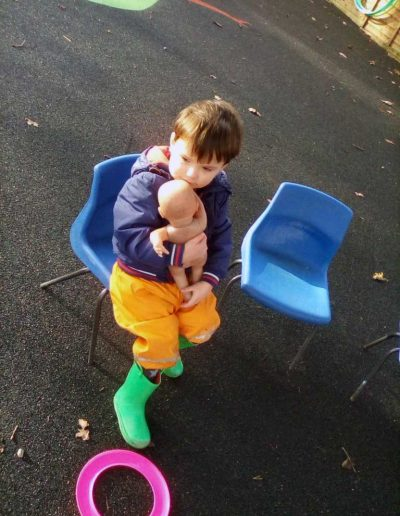 Oakwood Community Pre-school | Gallery | Child playing with a toy doll outside