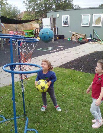 Oakwood Community Pre-school | Gallery | Throwing ball in basket net