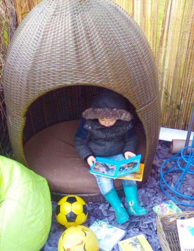 Oakwood Community Pre-school | Gallery | Reading outside in reading nest