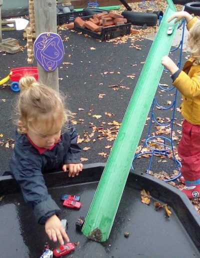 Oakwood Community Pre-school | Gallery | Playing with cars going down ramp outside