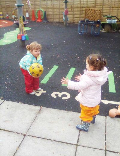 Oakwood Community Pre-school | Gallery | Two children playing catch with a ball