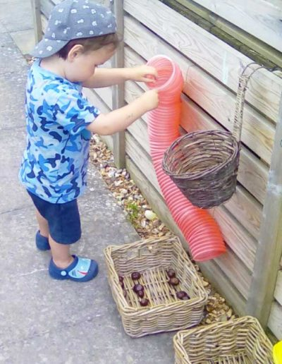 Oakwood Community Pre-school | Gallery | Child dropping conkers through a tube