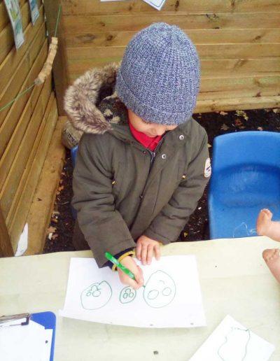 Oakwood Community Pre-school | Gallery | Child drawing on a piece of paper outside