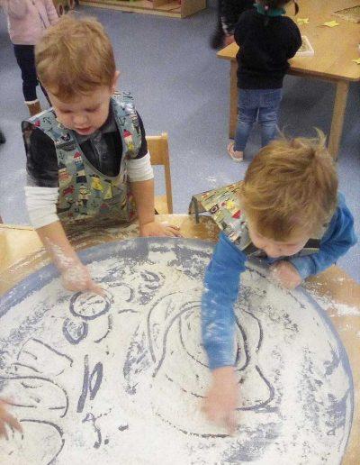 Oakwood Community Pre-school | Gallery | Children drawing in flour