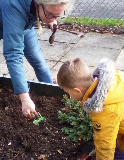 Oakwood Community Pre-school | Gallery | Child and staff looking at veg patch