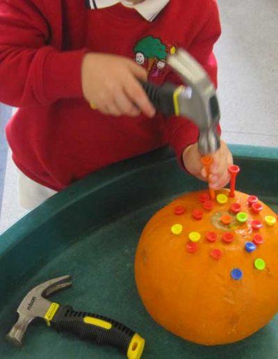 Oakwood Community Pre-school | Gallery | Child hammering tees into pumpkin