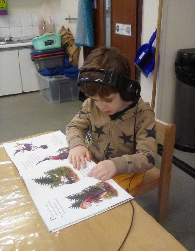 Oakwood Community Pre-school | Gallery | Child listening to story whilst turning pages
