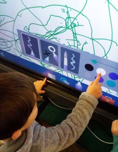 Oakwood Community Pre-school | Gallery | Child using interactive screen for drawing