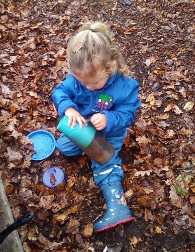 Oakwood Community Pre-school | Gallery | Child playing with autumn leaves