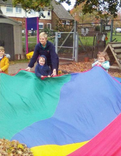 Oakwood Community Pre-school | Gallery | Children playing with colourful parachute