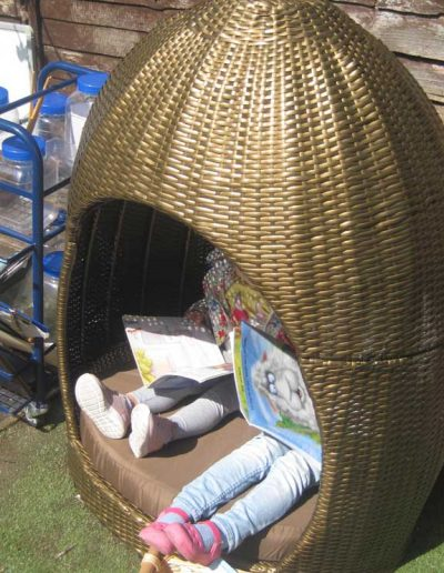 Oakwood Community Pre-school | Gallery | Children reading in the next outdoors sunny