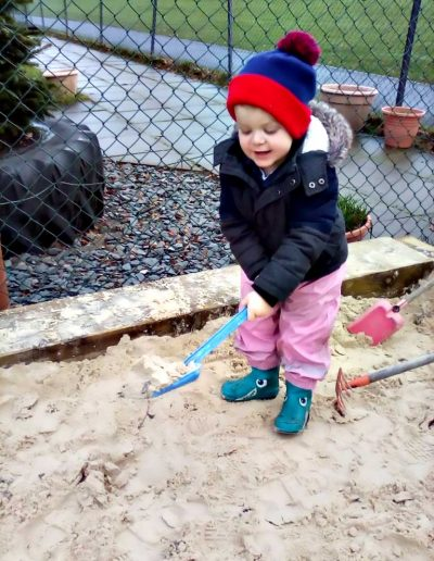 Oakwood Community Pre-school | Gallery | Child playing in the sandpit outside