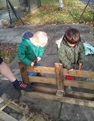 Oakwood Community Pre-school | Gallery | Children pretend sawing wood pallets