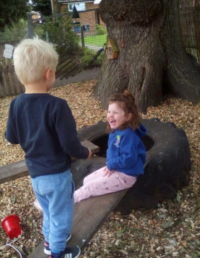 Oakwood Community Pre-school | Gallery | Children laughing with each other outside