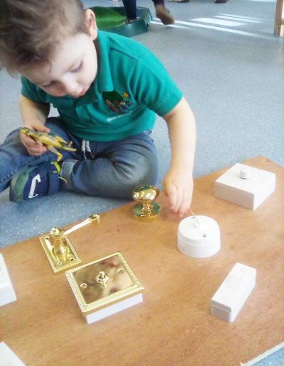 Oakwood Community Pre-school | Gallery | Child playing with switches and door handles