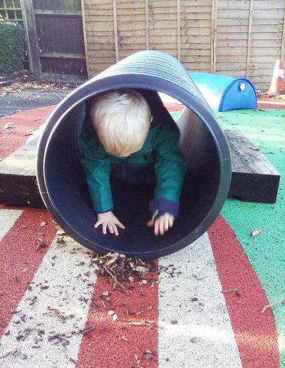 Oakwood Community Pre-school | Gallery | Child moving through a tunnel