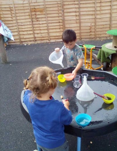 Oakwood Community Pre-school | Gallery | Children playing with water outside