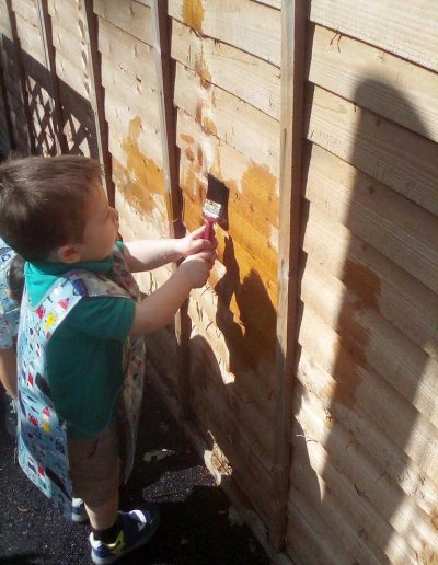 Oakwood Community Pre-school | Gallery | Child painting water on the fence
